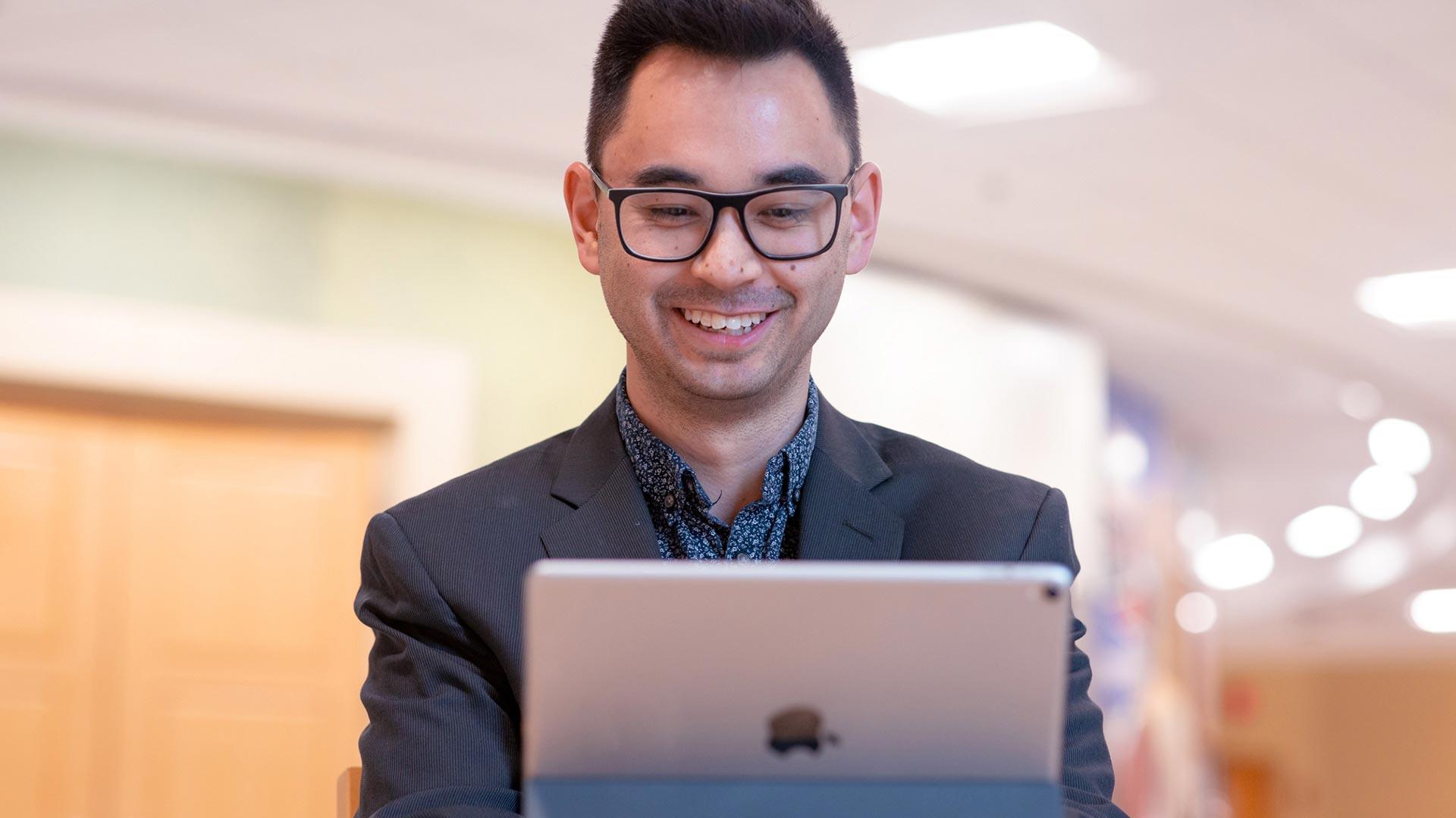 Smiling man looking at an iPad