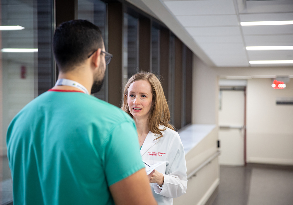 A nurse practitioner consults with a doctor in the halls of a hospital.