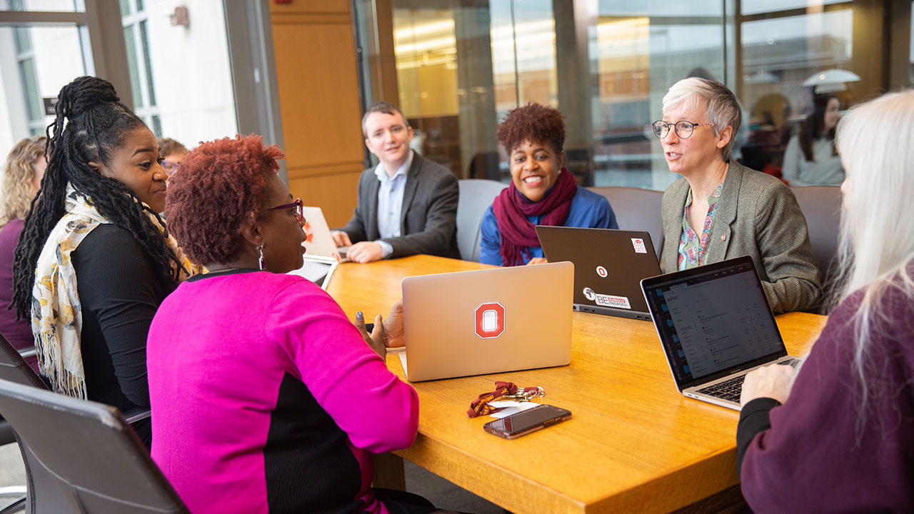 A group of professionals collaborate around a conference table.