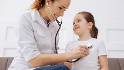 Nurse checking heart beat of young girl