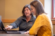 A Glenn College advisor shows a student online resources on a laptop.